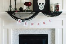 an elegant Gothic fireplace with a skeleton artwork, black tulle, black pillows, skeleton bones, candles and red roses