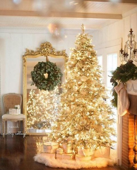 a creative gold pre lit Christmas tree with white ornaments and a faux fur skirt