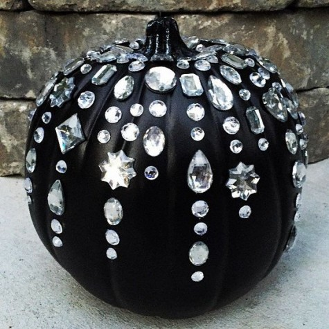 a matte black pumpkin with large crystals all over it is a cute and glam idea for a chic Halloween party