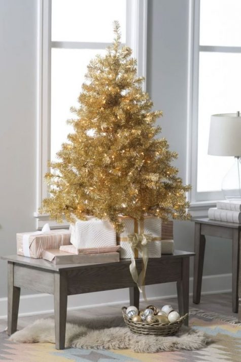 a gold Christmas mini tree with lights on a table is a stylish idea, and ornaments in a basket under it