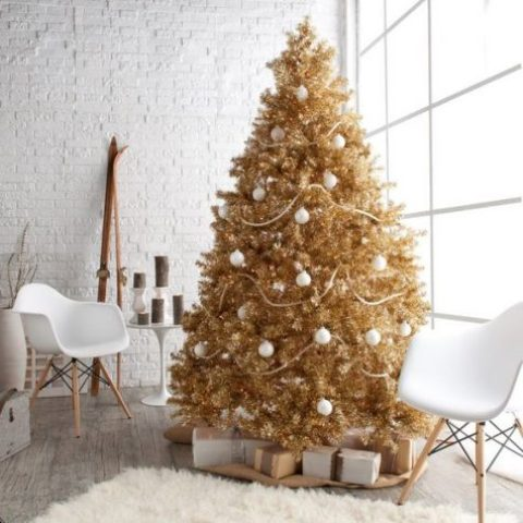 a gold Christmas tree decorated with white ornaments looks bold and unusual