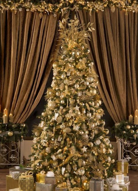 a luxurious Christmas tree all covered with gold ornaments, lights and ribbons plus metallic gift boxes