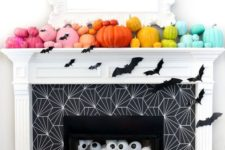 10 a bold Halloween fireplace with super colorful pumpkins on the mantel, bats and oversized eyeballs in the fireplace