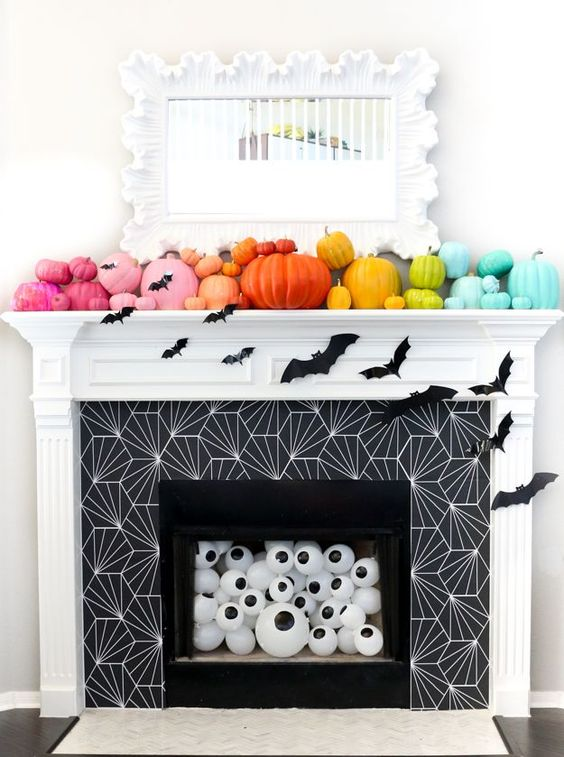 a bold Halloween fireplace with super colorful pumpkins on the mantel, bats and oversized eyeballs in the fireplace