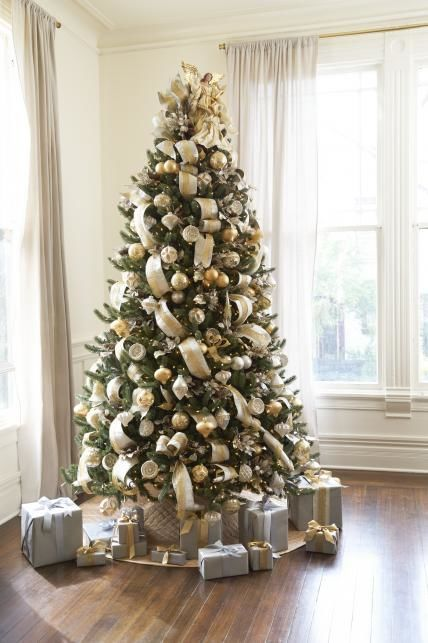 a green Christmas tree with lights decorated with gold and silver ornaments and ribbons plus a bow on top