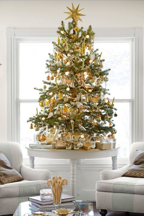 a tabletop Christmas tree with white and lots of gold ornaments and a large star topper for a festive feel