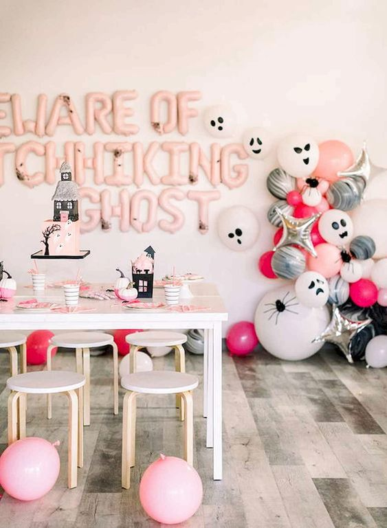 pink, white and black Halloween party decor with lots of balloons, letters and haunted houses here and there