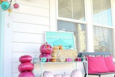 12 a bright Halloween porch with hot pink and light pink pumpkins, a turquoise sign, hay and bright pumpkins over the door
