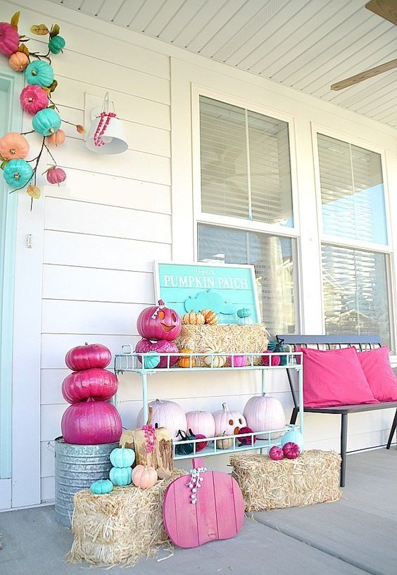 a bright Halloween porch with hot pink and light pink pumpkins, a turquoise sign, hay and bright pumpkins over the door