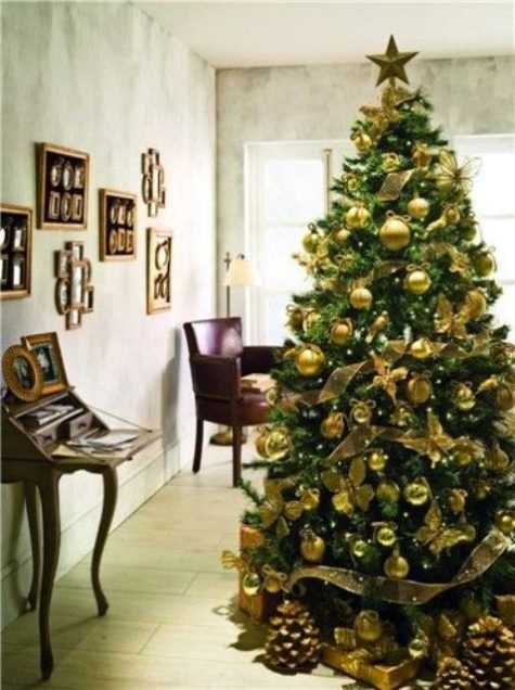 an emerald tree with gold ornaments looks chic and contrasting, gilded pinecones and gift boxes add a shiny touch