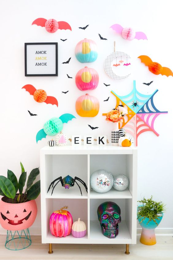 a colorful Halloween bar cart with gradient pumpkins, paper bats and spiderwebs on the wall and colorful pumpkins