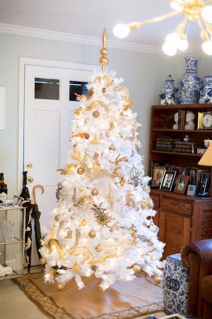 a white Christmas tree with lots of gold ornaments and ribbons plus a gold topper looks magical and bold