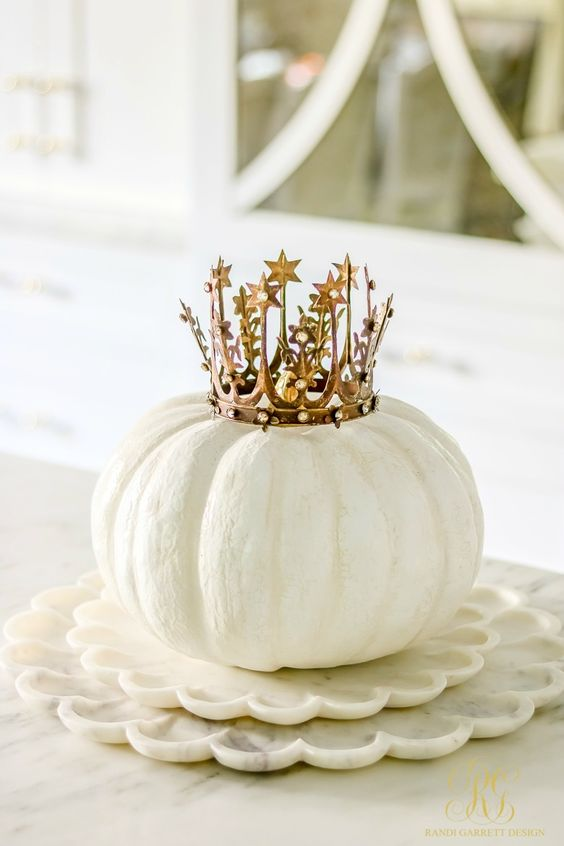 a white pumpkin topped with a beautiful crown is a cute and glam decoration or even a centerpiece