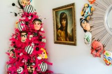 14 a fuchsia Halloween tree with mask decor and a matching wreath make the space super bold and bright