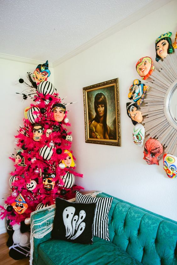 a fuchsia Halloween tree with mask decor and a matching wreath make the space super bold and bright