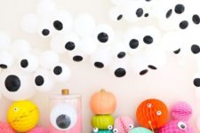 15 a bright Halloween food and drink station with lots of googly eyes, colorful paper balls and glasses
