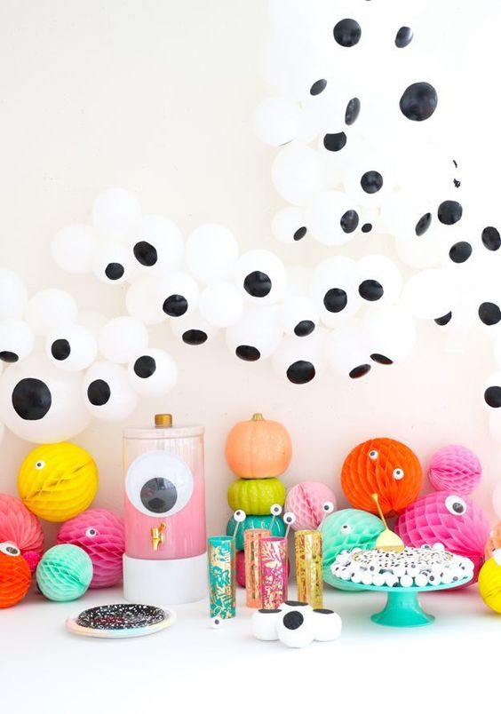 a bright Halloween food and drink station with lots of googly eyes, colorful paper balls and glasses