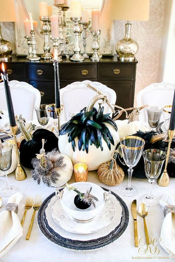 a glam black and gold Halloween tablescape with whiet as a base, feathered pumpkins, glitter ones and gold cutlery
