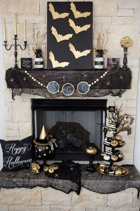 a glam black and gold mantel and fireplacewith a bunting, a sign, candles, pumpkins and black cheesecloth