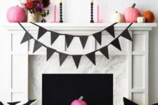 16 a stylish black and white Halloween fireplace with pink and orange pumpkins and a bright floral centerpiece