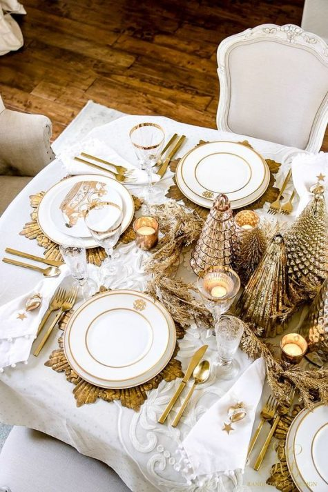a super glam gold and white Christmas table with a shiny centerpiece, candles, sunburst placemats, cutlery and gold rim glasses