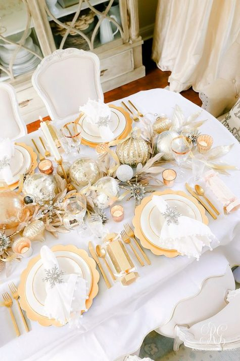 a shiny and bright gold and white Christmas table setting with gold chargers, metallic ornaments, branches, gold cutlery and silver elements
