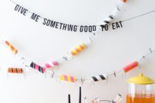 19 colorize your Halloween party with a colorful toilet paper roll garland and bright pumpkins and tablecloths