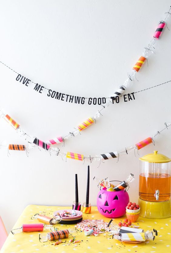 colorize your Halloween party with a colorful toilet paper roll garland and bright pumpkins and tablecloths