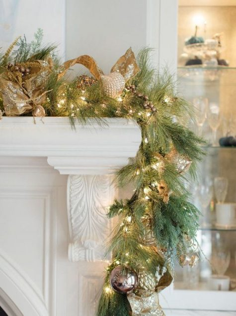 a cool garland of evergreens, lights, gold ornamentsand ribbons looks very glam