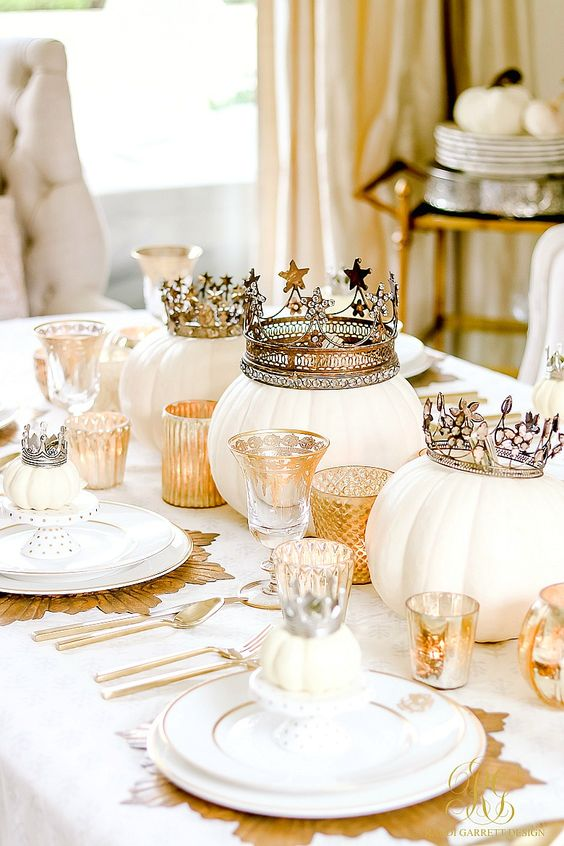 a gold and white glam Halloween tablescape with pumpkins in crowns, gold touches and gold placemats