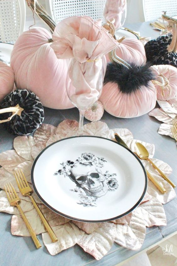 a gorgeous glam Halloween tablescape with a skull plate, a leafy placemat, pink velvet pumpkins and touches of black