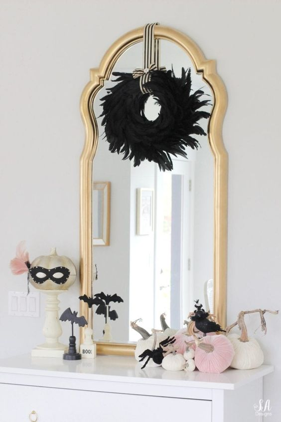 a mirror in a gilded frame, a blakc feather wreath, black bats and spiders, white and pink pumpkins plus a pumpkin in a mask
