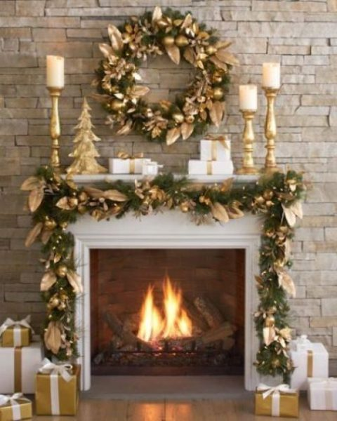 a stylish fireplace with a gold wreath of fruit and leaves, a matching garland over the fireplace and gold candleholders