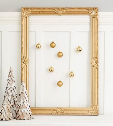 a vintage gold frame with gold ornaments hanging inside is a great decoration