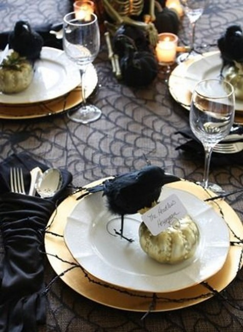 an elegant place setting in black and gold, with faux birds and gold pumpkins is a gorgeous idea for a dinner party