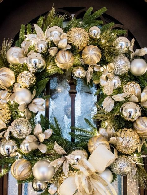an evergreen wreath with gold and silver ornaments is a timeless idea for a front door