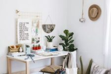 a boho chic home office nook with a white desk, macrame artworks, potted plants and signs
