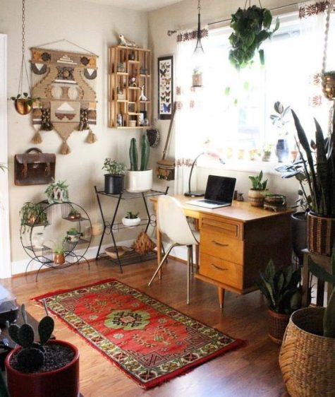 a boho chic home office with a retro wooden desk, a boho rug, a folksy artwork o the wall, lots of potted plants, cacti and succulents