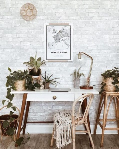 a boho home office nook with a catchy white desk, a rattan chair, macrame touches and potted plants and greenery