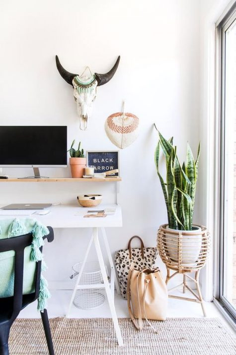 a boho home office with a white trestle desk, a rattan planter stand, a jute rug and boho decorations