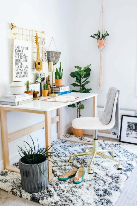 a boho meets glam home office with a boho rug, macrame and fringe, potted plants and lots of cacti