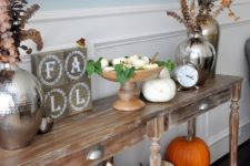 a bright Thanksgiving console table with white and orange pumpkins, dried eucalyptus and firewood