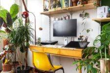 a bright boho home office with open shelving, a retro desk, a yellow chairs and lots of potted plants here and there
