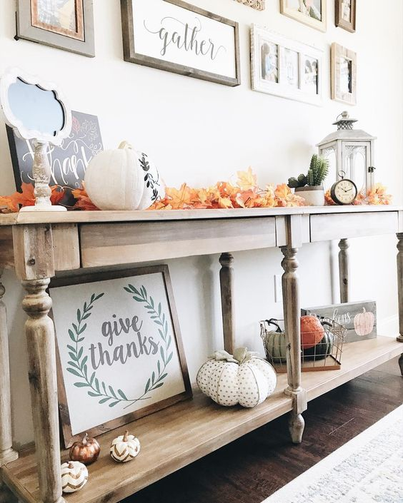 a bright fall or Thanksgiving console table with colorful fall leaves, fabric or plastic pumpkins and a lantern