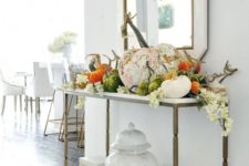 a chic console table with fake plastic and fabric pumpkins, white white blooms and a dried herb wreath over the table