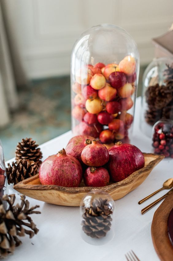 a cloche filled with small fresh apples almost to the top is a cool idea for fall decor and will do for Thanksgiving