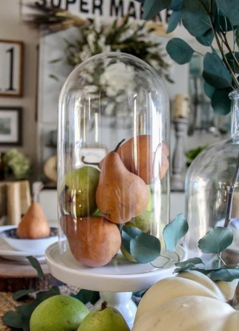 a cloche with fake fruits is an ideal farmhouse display for fall and Thanksgiving, great as a centerpiece