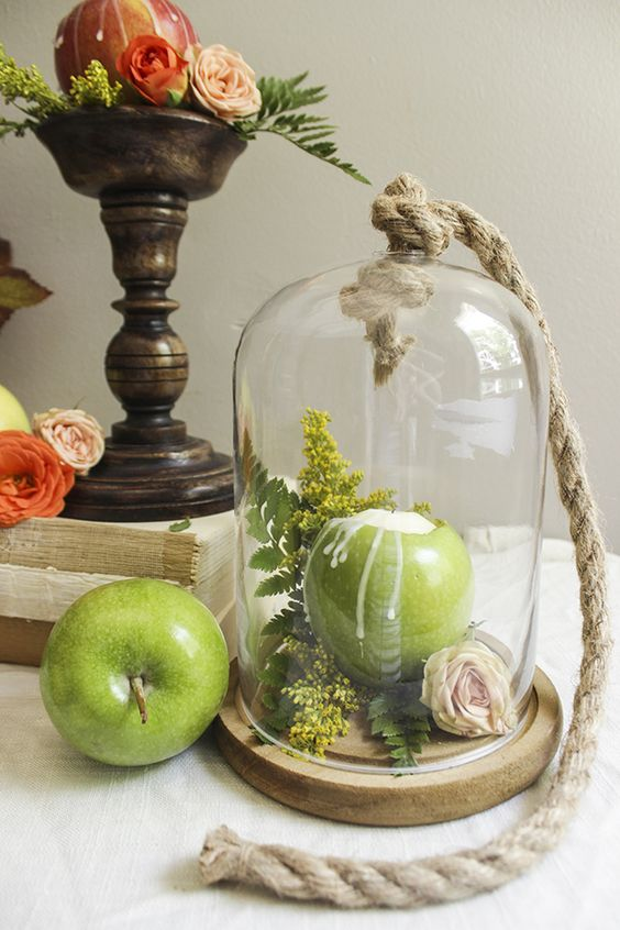 a cloche with rope and with greenery, ferns and a blush bloom inside plus a green apple as a candleholder