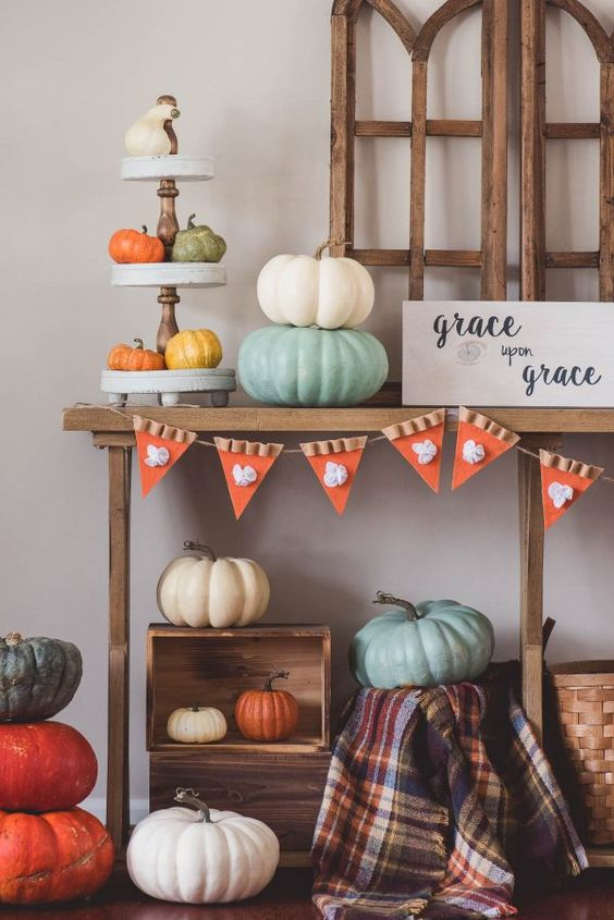 a colorful Thanksgiving console table with bright painted pumpkins, a cool garland, a plaid blanket, pumpkin pie banner and wooden crates