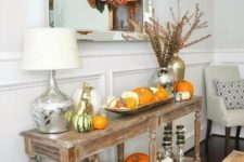 a colorful Thanksgiving console with bright and neutral pumpkins, candles, dried eucalyptus and a green blanket